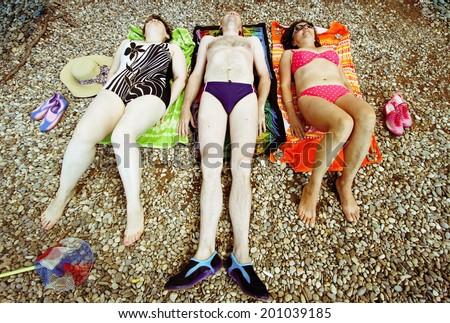 Three people sunbathing on stone beach. - stock photo
