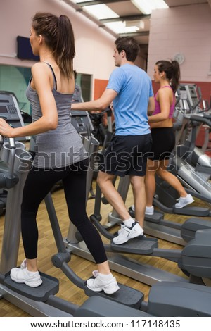 Three people training on  step machines in gym