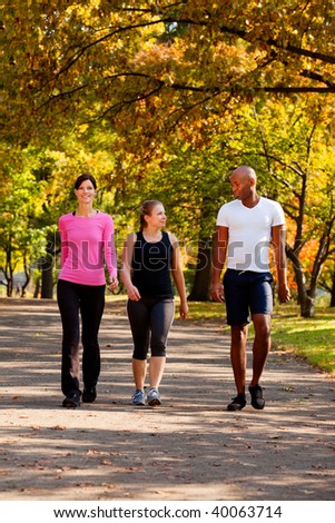 Three people walking in a park, getting some exercise - stock photo