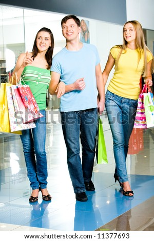 Three people walking in the shopping mall - stock photo