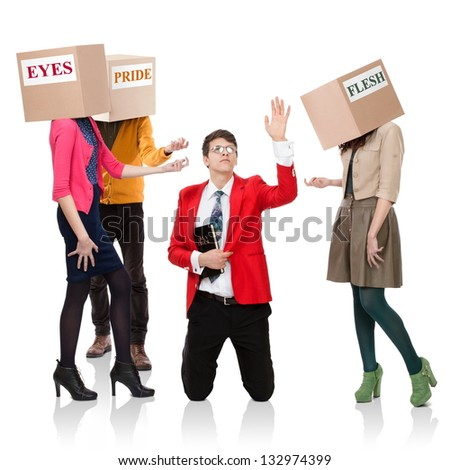 Three people with boxes in the head that call a young man with a Bible. Concept of the call of temptations. - stock photo