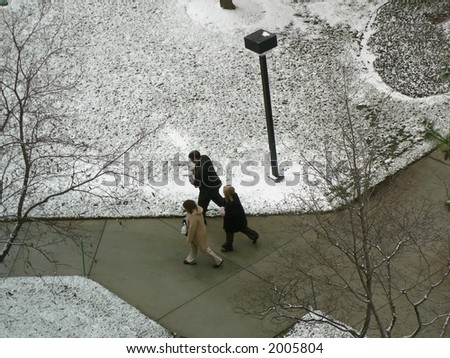 Three people with carryout lunches in snow. - stock photo