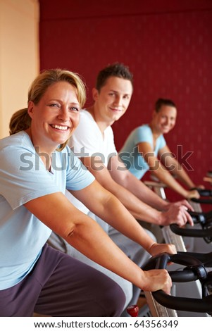 Three people working out on bikes in gym - stock photo