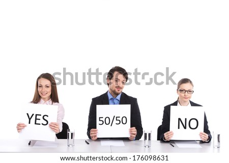 three person sitting at table holding signs. two woman and man selling legally - stock photo