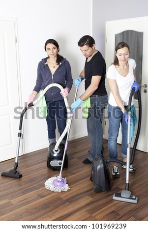 Three persons cleaning a house