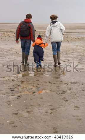 Three persons (woman, man and boy) in a rubber boots
