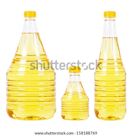 Three pet bottles (thick one and small one and thin one) filled with yellow vegetable oil and with yellow caps isolated on white - stock photo