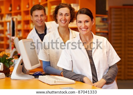 Three pharmacists at a counter in a pharmacy - stock photo