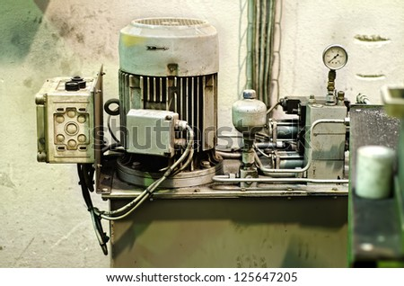 Three-phase industrial, electric motor used for producing high-pressure in a traditional factory - stock photo