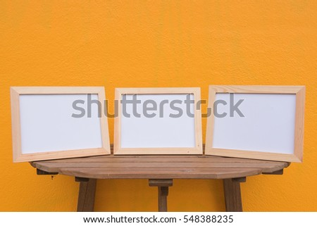 three photo Frame on a wooden on Yellow background .