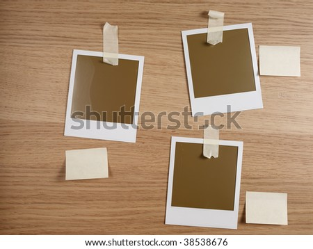 three photos taped on wooden desktop - stock photo