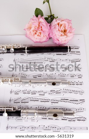 Three Piccolo's on top of sheet music - stock photo