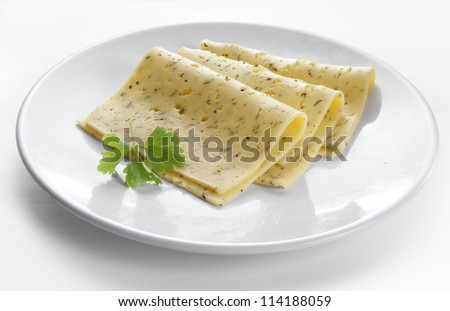 Three pices of cheese with fresh parsley on the white plate