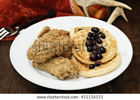 Three pieces of deep fried chicken with waffles served with fresh blueberry sauce over a rustic background. Extreme shallow depth of field. - stock photo