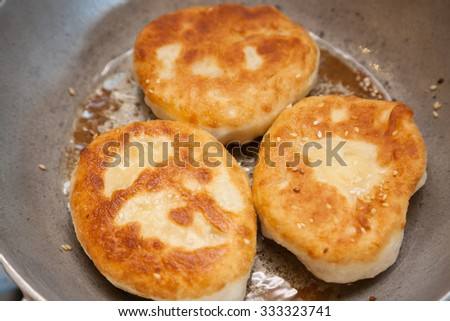 Three pieces of fried bhatura in pan - stock photo