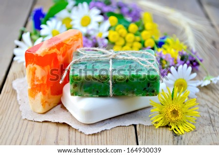Three pieces of homemade soap on a piece of paper, chamomile flowers, tansy, elecampane on the background of wooden boards - stock photo