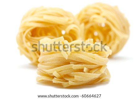 Three pieces of pasta - tagliatelle. Closeup. Front rests, rear stands vertically. The background is blurred. Isolated on white background.
