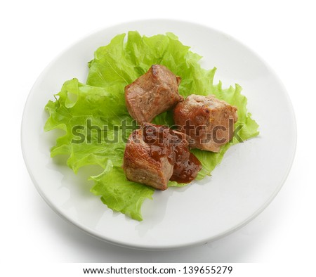 Three pieces of roasted meat with fresh lettuce and tomato sauce on the white plate