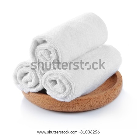 three pieces of white towels on wooden plate - stock photo