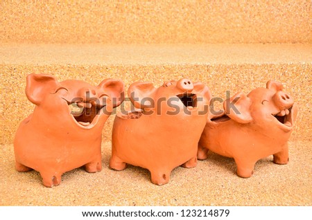 Three Pig statues laugh facing the same way. - stock photo