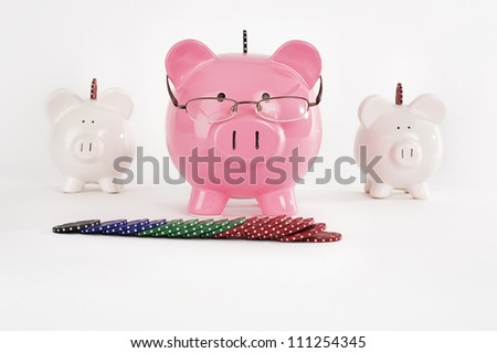 Three piggy banks with playing poker chips - stock photo