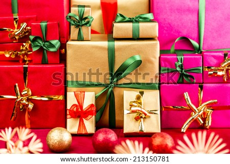Three piles of plain Xmas presents grouped by color. Red, gold and magenta. All with bow knots. Stars and baubles on red foreground. Shallow depth of field. Vibrant colors.  - stock photo