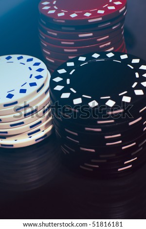 Three piles of poker chips on a reflective surface. - stock photo