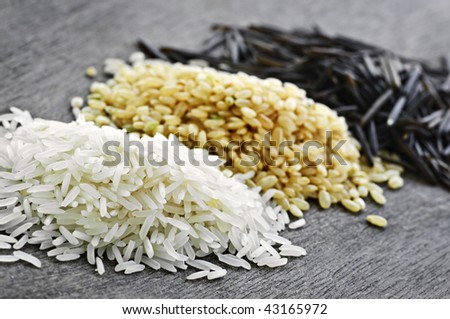 Three piles of white, brown and wild black uncooked rice - stock photo