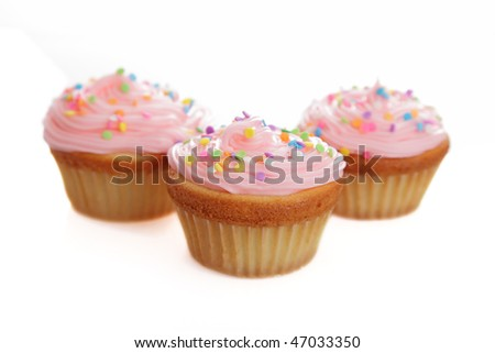 Three pink cupcakes on a white background. - stock photo