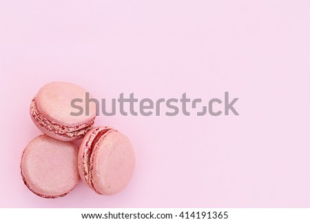 Three pink macarons over a pink background with copy space available. - stock photo