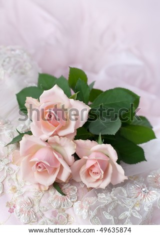 Three pink roses on wedding lace (shallow depth of field, copy space) - stock photo