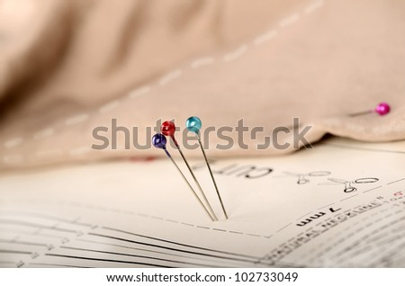 Three pins on a pattern with material - stock photo