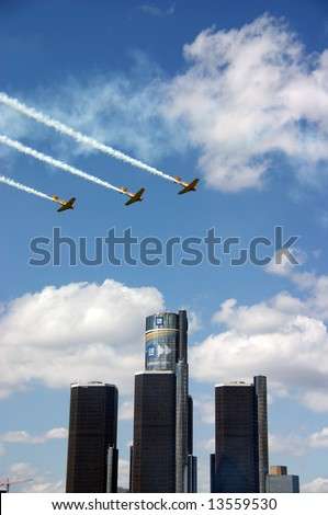 Three planes flying over the Renaissance Center in Detroit, MI during the Red Bull Air Races. - stock photo