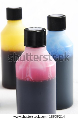 three plastic bottles with different coloured ink in each - stock photo
