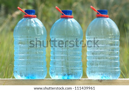 Three plastic cans with cold ecologically pure drinking water - stock photo