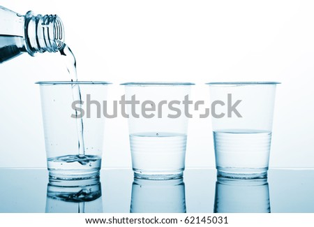 Three plastic glasses with water. The water following from a bottleneck in a glass. Blue-White duotone image. - stock photo