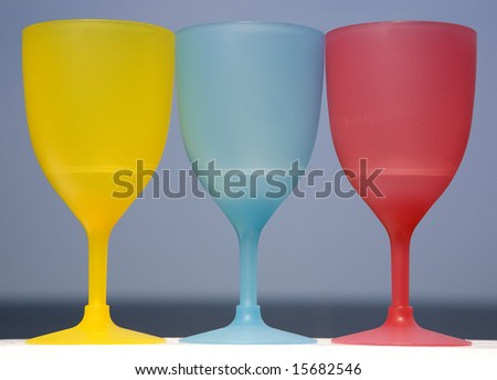 Three plastic goblets sitting on a white deck railing that are also the three primary colors in art.
