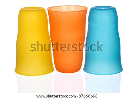 three plastic multi-colored glasses isolated on a white background. Plastic glass of various color isolated on white background - stock photo