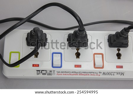 Three plugs plugged into electric power bar in line - stock photo
