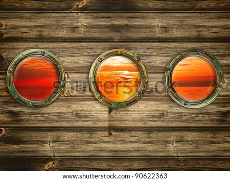 three portholes with view at the sunrise - stock photo