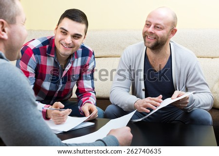 Three positive males with documents at agency - stock photo