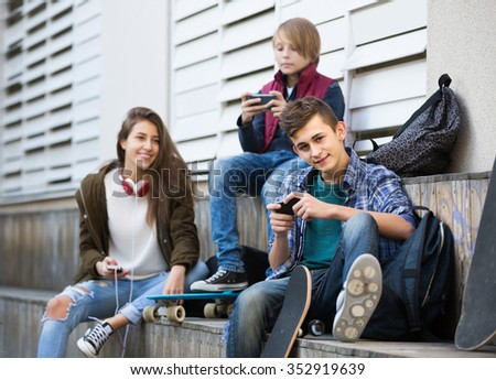 Three positive spanish teenagers with smartphones in autumn day outdoors  - stock photo