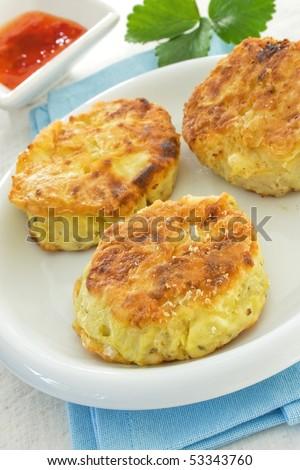 Three potato cakes on a white plate - stock photo