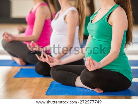 Three pregnant women is doing exercise at gym. - stock photo