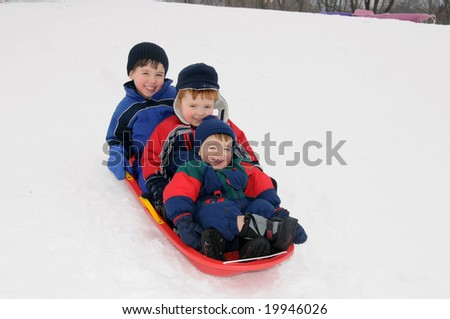 Three preschool-aged boys have fun together sliding downhill on a pleasant winter day. - stock photo