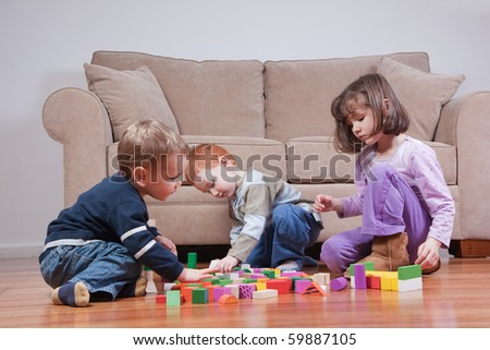 Three preschooler kids playing with blocks - stock photo