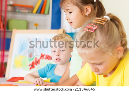 Three preschoolers in the classroom - stock photo