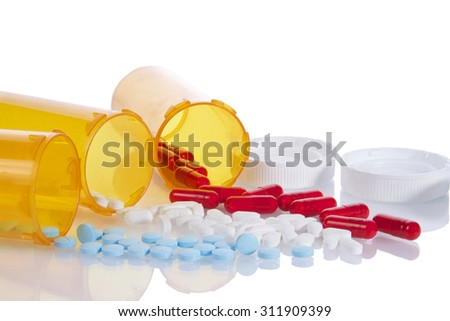 Three Prescription bottles lined up on their sides spilling medication pills out onto a reflective surface isolated on a white background. Depicting multiple medications, overwhelming to keep track of - stock photo