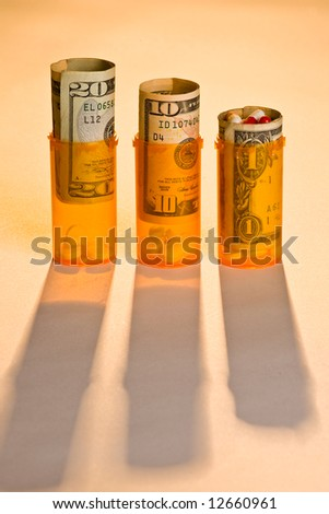 Three prescription pill bottles with pills and money, warm back light and long shadows - stock photo