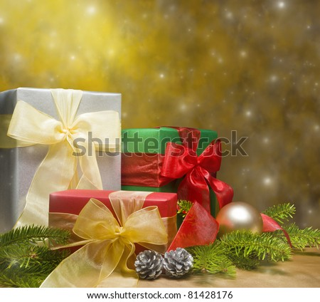 Three presents decorated with gold satin and Christmas decoration, with space for advertising text - stock photo